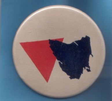 [Badge depicting a pink triangle and map of Tasmania] – Tasmanian Gay and Lesbian Rights Group (TGLRG), c.1988, 2-12-1